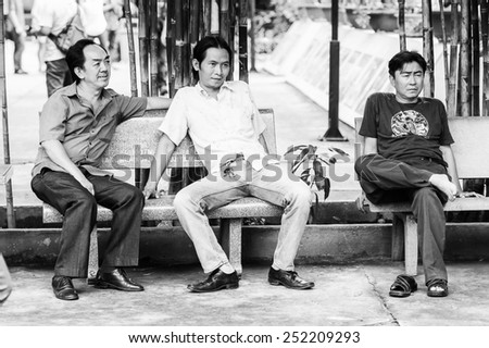 HO CHI MINH, VIETNAM - SEP 20, 2014: Unidentified Vietnamese men sit on a bench. 90% of Vietnamese people belong to the Viet ethnic group