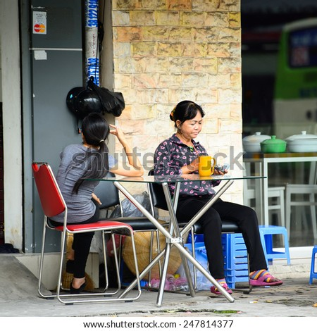 HO CHI MINH, VIETNAM - SEP 20, 2014: Unidentified Vietnamese woman over the table on the street in the street. 90% of Vietnamese people belong to the Viet ethnic group