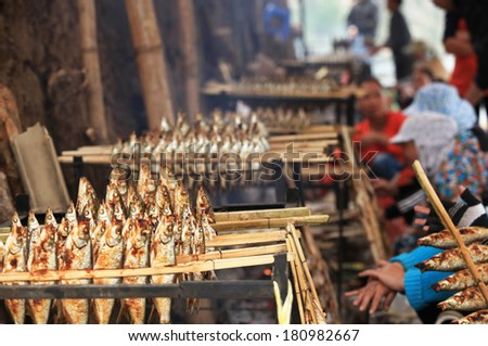 HOA BINH, VIETNAM - MAR 4, 2014: Unidentified local women roasting caught fishes to sell to visitors at an island on Song Da hydro-power lake.