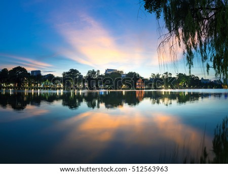 Hoan Kiem lake ( Ho Guom, Sword lake), the center of Hanoi capital, Vietnam at twilight. Willow branches on foreground