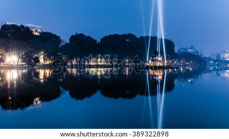 Hoan Kiem Lake (Lake of the Returned Sword) and the Turtle Tower among laser lighting show at blue hour. Blue light rays display at historic center of Hanoi, Vietnam. The tower reflected in the lake