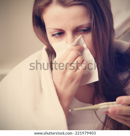 hoarse girl blows her nose and looks temperature