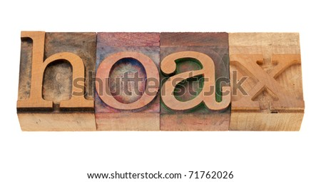 hoax - word in vintage wooden letterpress printing block, stained by color inks, isolated o n white