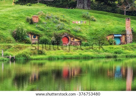 hobbit holes in hobbiton movie set reflecting in a small lake. Taken in New Zealand. - stock photo