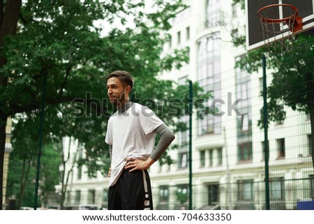 Hobby, leisure, sports and healthy lifestyle. Happy unshaven young man holding hand on his waist relaxing after streetball game at outdoor court in urban setting with modern building in background