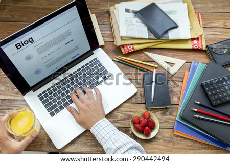 Hobby time. Concept man working on computer unusual handcrafted rough wooden desk overhead top view keeping juice many office supplies creative disorder focus on plate with fresh strawberry food glass - stock photo