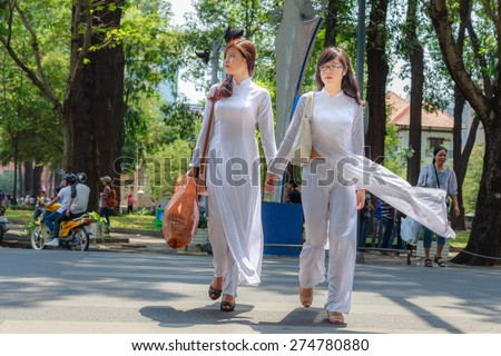 HOCHIMINH CITY, VIETNAM, FEBRUARY 16 : unidentified Vietnamese girls wearing white Ao dai on the street on February 16, 2014. Ao dai is famous traditional Custume for women in Vietnam.