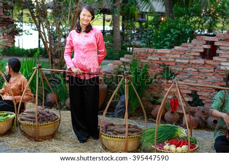 Hochiminh City, Vietnam - March 5, 2016 : salesgirl with her bamboo basket full of vegetables in the culinary fair at the Van Thanh tourist area, Ho Chi Minh City which is modeled on the traditional