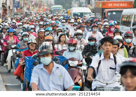HOCHIMINH, VIETNAM - FEB 9, 2015: A lot of motorcyclists and vehicles drive along Quang Trung Street during rush hours. The main means of transport in Vietnam is motorcycle. - stock photo