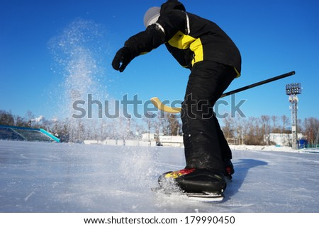Hockey amateur boy player braking on the rink with ice spatter
