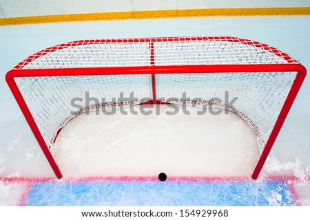 Hockey goal with puck on red line. View from above - stock photo