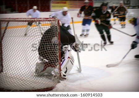 Hockey goalie in generic black equipment protects gate