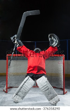 Hockey goalkeeper standing elated with arms raised up above her head - stock photo