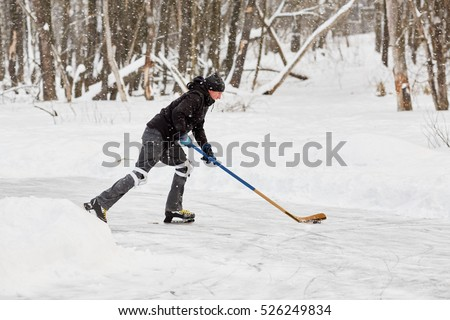 Hockey player carries puck at outdoor skating rink in park.