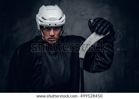 Hockey player in a black sportswear and white helmet holds the gaming stick on grey background.