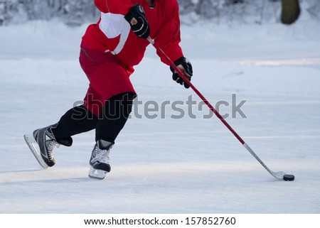 Hockey player skating on ice - stock photo