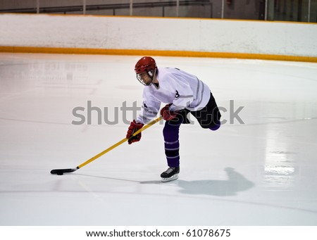 Hockey player taking a shot on net - stock photo
