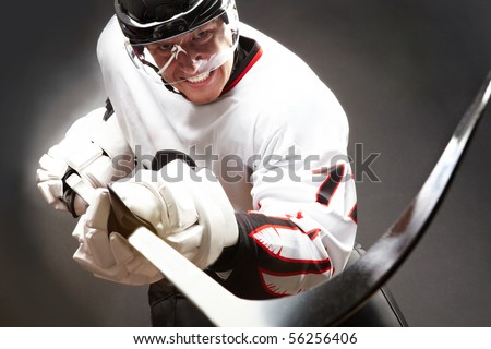 Hockey player with cruel facial expression pointing stick into camera - stock photo