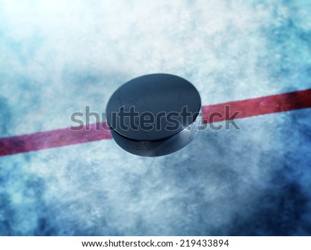 Hockey puck in the middle above the ice and red line with lens flare around puck. - stock photo