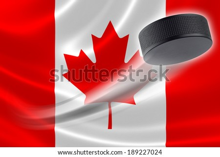 Hockey puck streaks across the flag of Canada, where the country is one of the world's major ice hockey nations. - stock photo