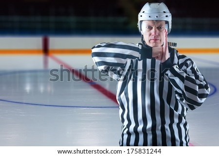 Hockey referee demonstrate boarding penalty. Ice rink on background - stock photo