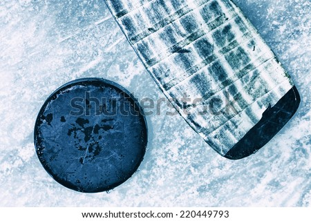 Hockey Stick and Puck. Background Surface of Outdoor Ice Rink Replete with Skate Marks.