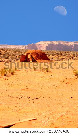 Hogan and Large moon over Monument Valley Arizona - stock photo