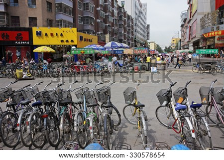 HOHOT, INNER MONGOLIA, CHINA - JULY 3, 2008: Dozens of bicycles - the most affordable transport for many residents - parked in the central business area - stock photo