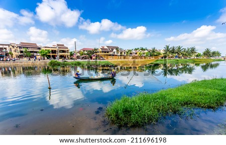 HOI AN, DANANG, VIETNAM - MAY 1, 2014 - Two unidentified men cleaning the canal in downtown. Hoi An is the World's intangible heritage and it attracts lots of tourists from many countries to visit. - stock photo