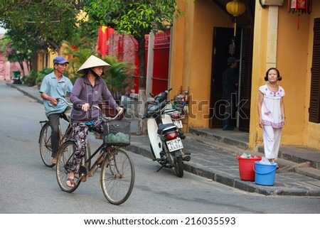 HOI AN, VIETNAM - APIRL 18: unidentified woman ride the bicycle in front of a buddhistic temple on APIRL 18, 2014 in Hoi An, Vietnam. Hoi An is a major touristic destination in Central Vietnam