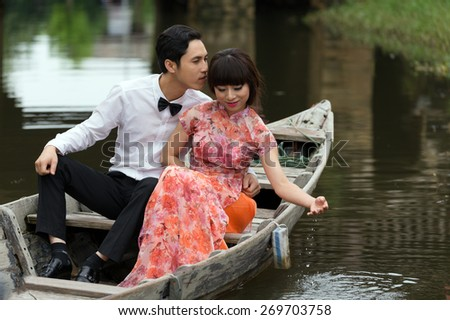 HOI AN, VIETNAM, DECEMBER 14, 2014: A young couple is celebrating his wedding on a wooden boat in the city of Hoi Han, Vietnam. - stock photo