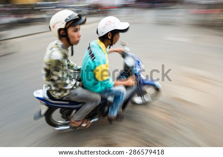 HOI AN, VIETNAM - DECEMBER 4: Two men in helmets riding bike. The most popular means of transport in this country. 4th place in bike usage in world. December 4, 2012, Hoi An, Vietnam, Asia. - stock photo