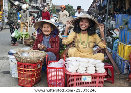 HOI AN - VIETNAM - JANUARY 6, 2014 Two friendly market-woman selling rice and food at a local market in Hoi An, Vietnam. They sit on the crowdy streets and offer their food. - stock photo