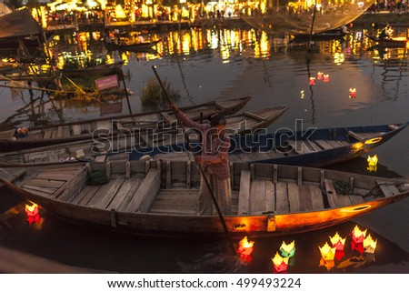 HOI AN, VIETNAM - MARCH 15 2016: Night view of a unidentified vietnamese woman on a boat that waiting for tourist at riverfront of Hoi An old town. Hoi An is declared a World Heritage Site by UNESCO