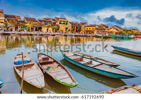 HOI AN, VIETNAM - MARCH 17, 2017: Traditional boats in front of ancient architecture in Hoi An, Vietnam. Hoi An is the World's Cultural heritage site, famous for mixed cultures & architecture.