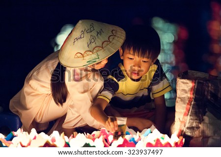 Hoi An, Vietnam - March 14, 2014: Vietnamese girl and boy are selling candles for tourists in Hoi An old town at night on March 14, 2014 in Hoi An, Vietnam.