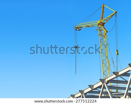 hoisting crane against the blue sky with space for text - stock photo