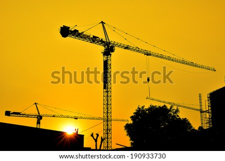 Hoisting crane silhouettes at sunset