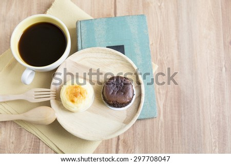 Hokkaido chocolate cheesecake with coffee cup with wooden background
