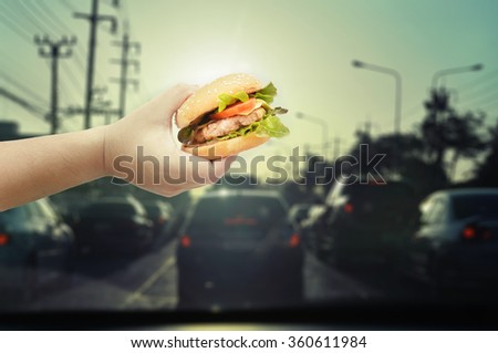 hold burger in car  - stock photo