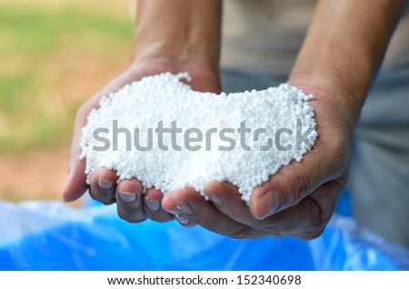 Hold of urea chemical fertilizer on farmer hand - stock photo
