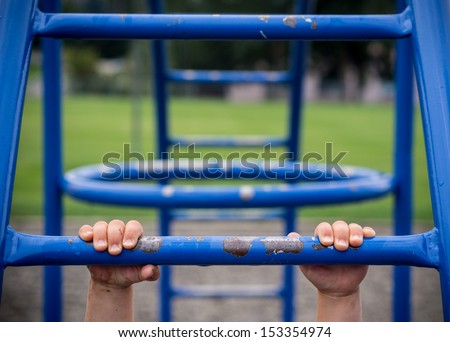 Hold on to monkey bars at playground - stock photo