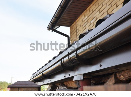 Holder gutter drainage system on the roof. Closeup of problem areas for plastic rain gutter waterproofing. - stock photo