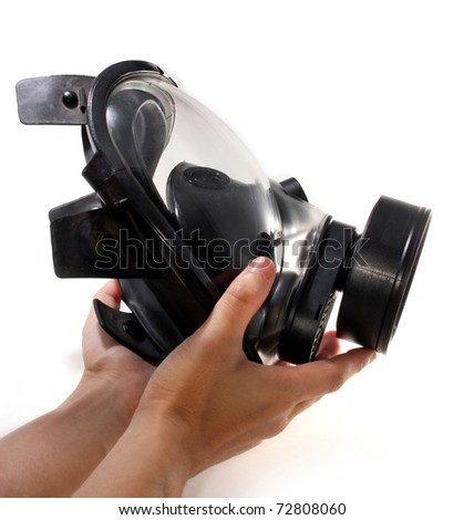 Holding a black gas mask in hands - stock photo