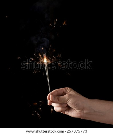 Holding a burning sparkler, low-key composition isolated over the black background