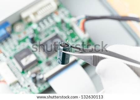 holding a capacitor with tweezers in front of a circuit board