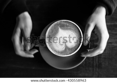 holding a coffee in black and white