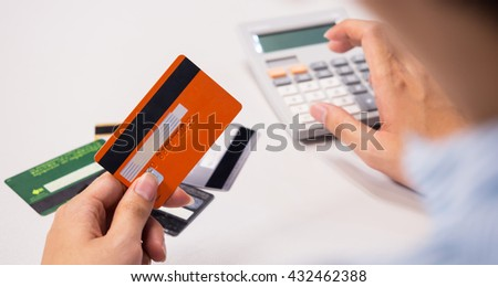 holding a credit card and payment calculate for credit card   - stock photo