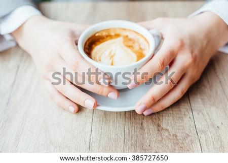 Holding a cup of coffee - stock photo