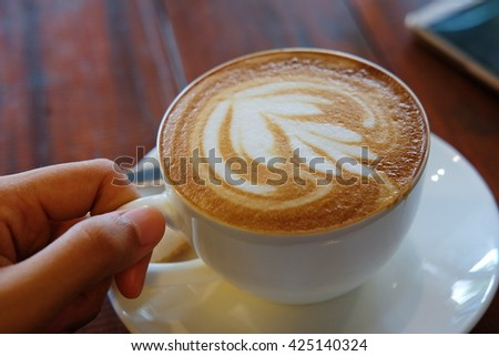 Holding a cup of fresh hot coffee on white plate and wooden background - stock photo